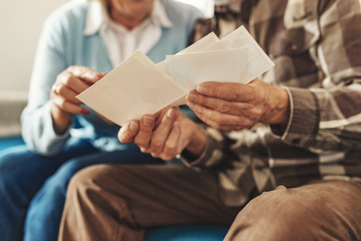 Cropped Image of Senior Couple Holding Up an Old Photos of Themselves When They Were Young While Sitting on Their Living Room. Concept of Active Playful Elderly During Retirement. Old People at Home Lifestyle