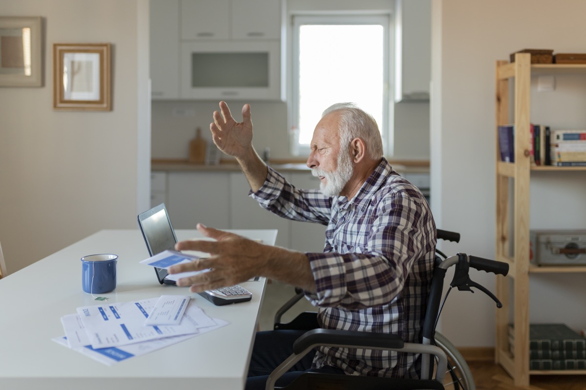 man Reading Bad News in Paper Letter Document, Troubled With Domestic Bills, Concerned About Bankruptcy Debt Money Problems. Tensed Senior Man Checking the Bills at Home While Using Laptop