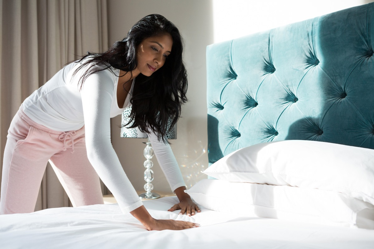 Woman making bed in morning