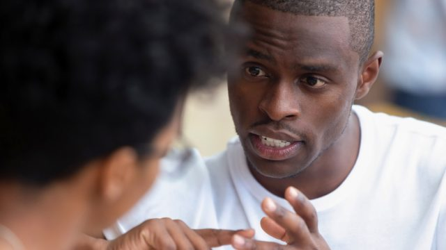 black man having a serious conversation with a woman, whose head is to the camera