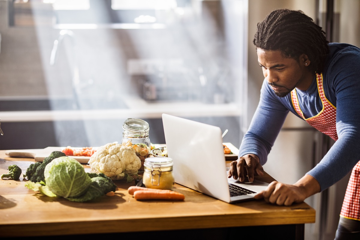 man using laptop while searching for the right lunch recipe in the kitchen.