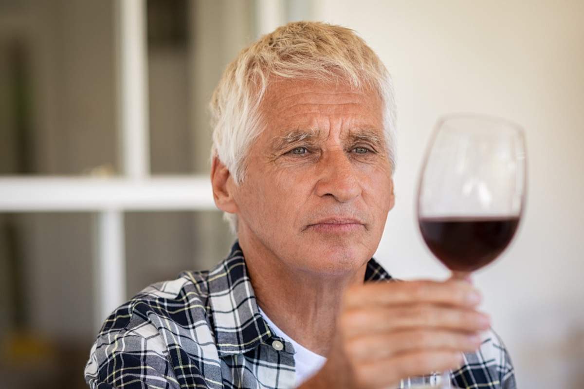 Senior man holding and looking through a glass of red wine.