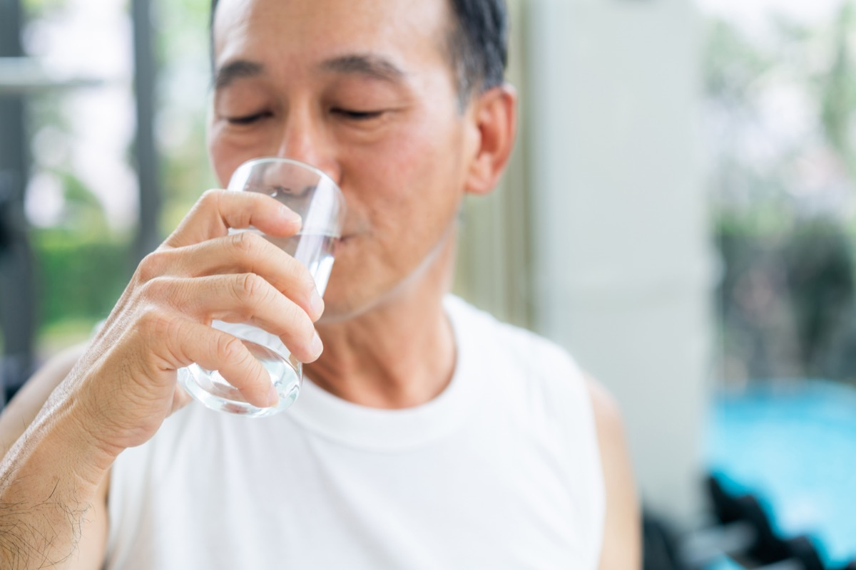Senior man drink mineral water in gym fitness center after exercise. Elderly healthy lifestyle.