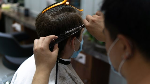 man getting haircut while wearing surgical mask