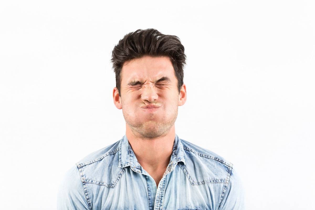 Young white man making a face while holding his breath amid white background