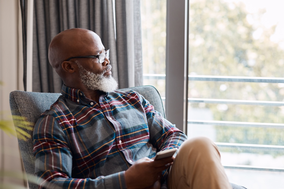 Shot of a mature man looking thoughtful while using a cellphone at home
