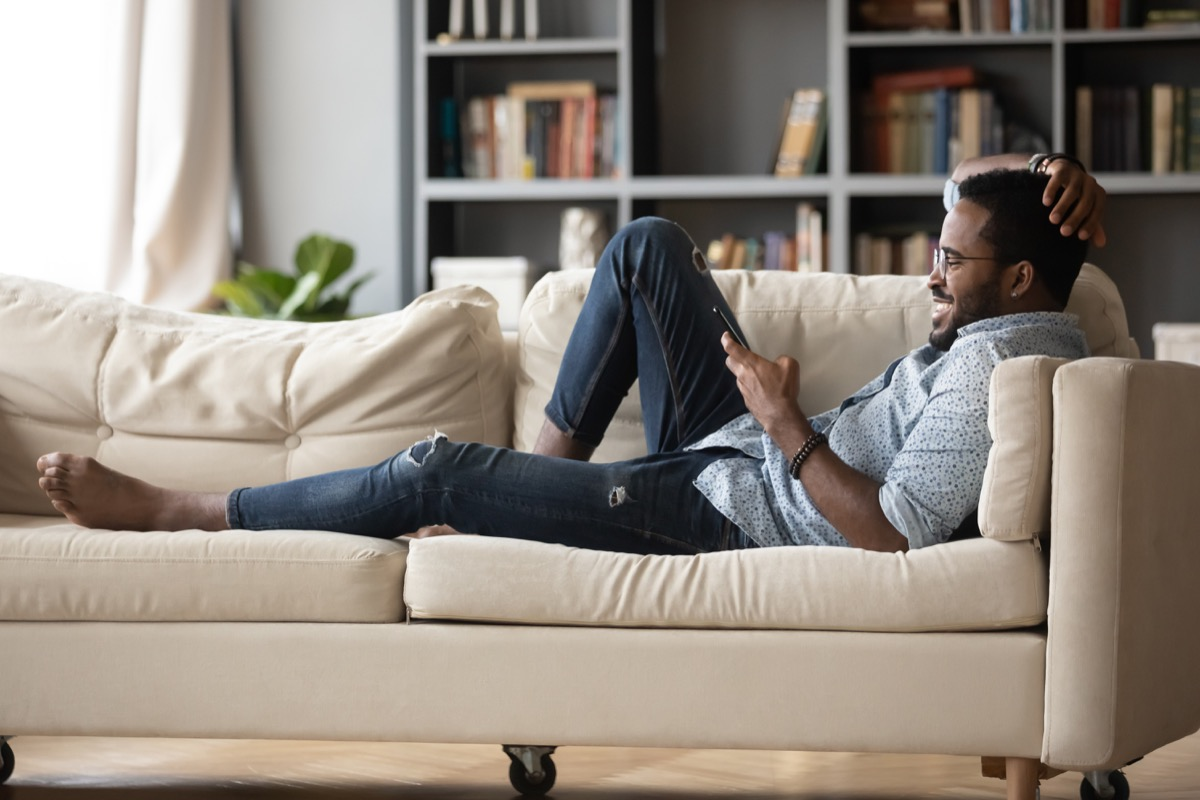 Full length relaxed young man in glasses lying on comfortable couch, enjoying spending weekend leisure time chatting in social network on phone with friends, watching funny videos.