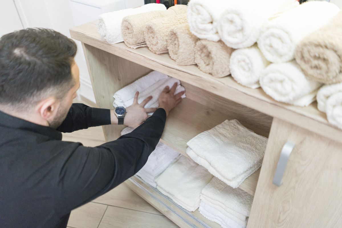 Man making space for clean towels in bathroom shelving unit