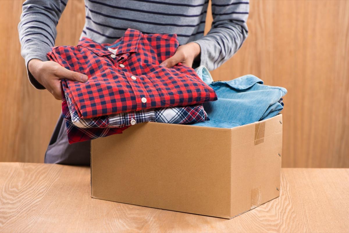 man putting clothing in cardboard box