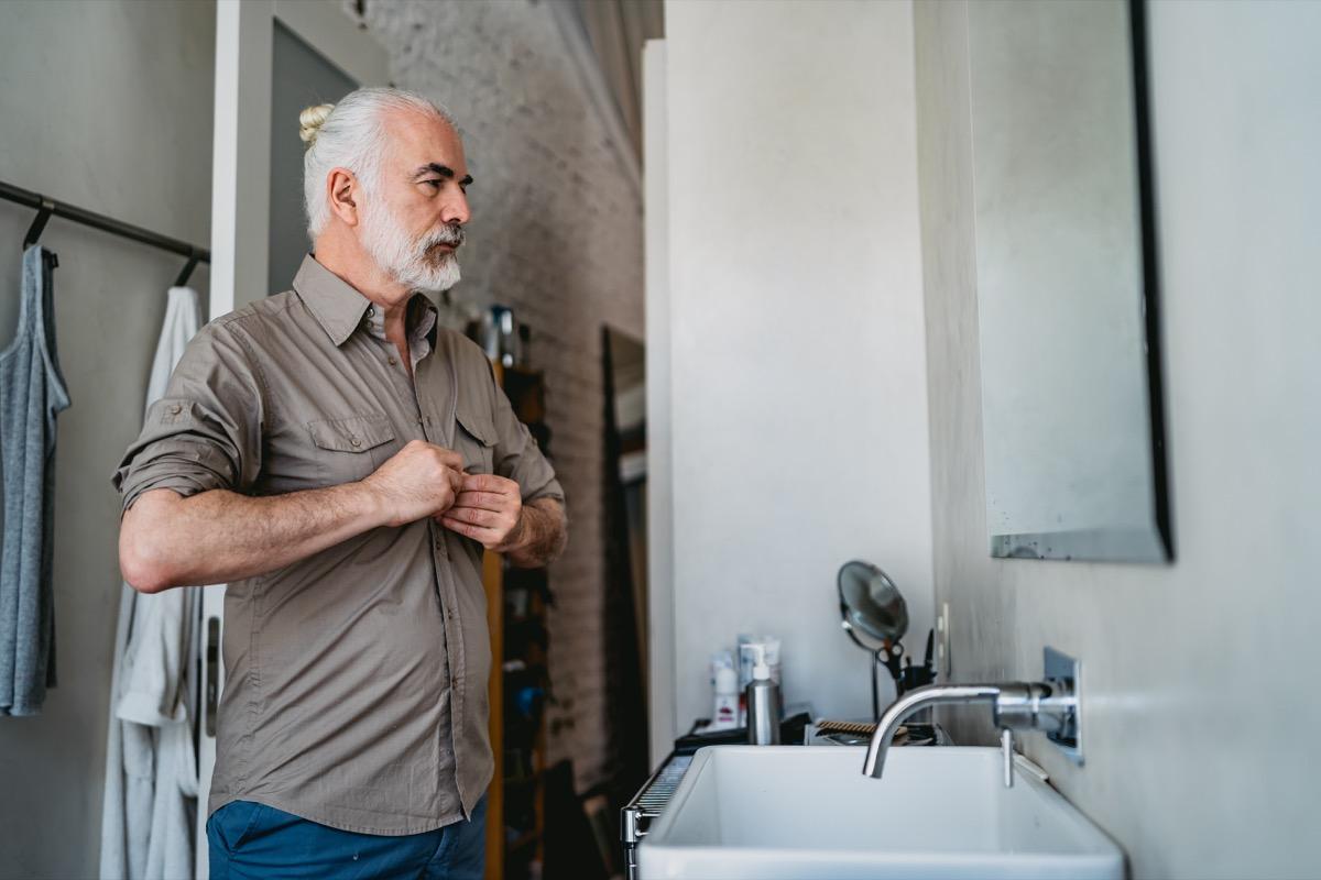 Senior handsome man dressing up in bathroom.