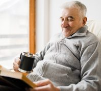 Senior man old sitting and Reading a book at the retirement nursing home with cup of tea in hand