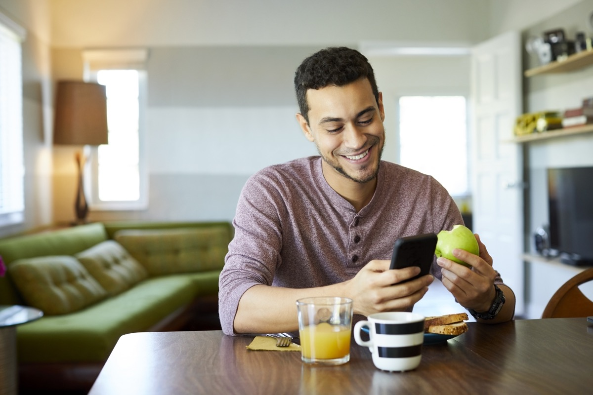 Smiling young man using smart phone at dining table. Male is having granny smith apple at home. He is enjoying social media and breakfast.