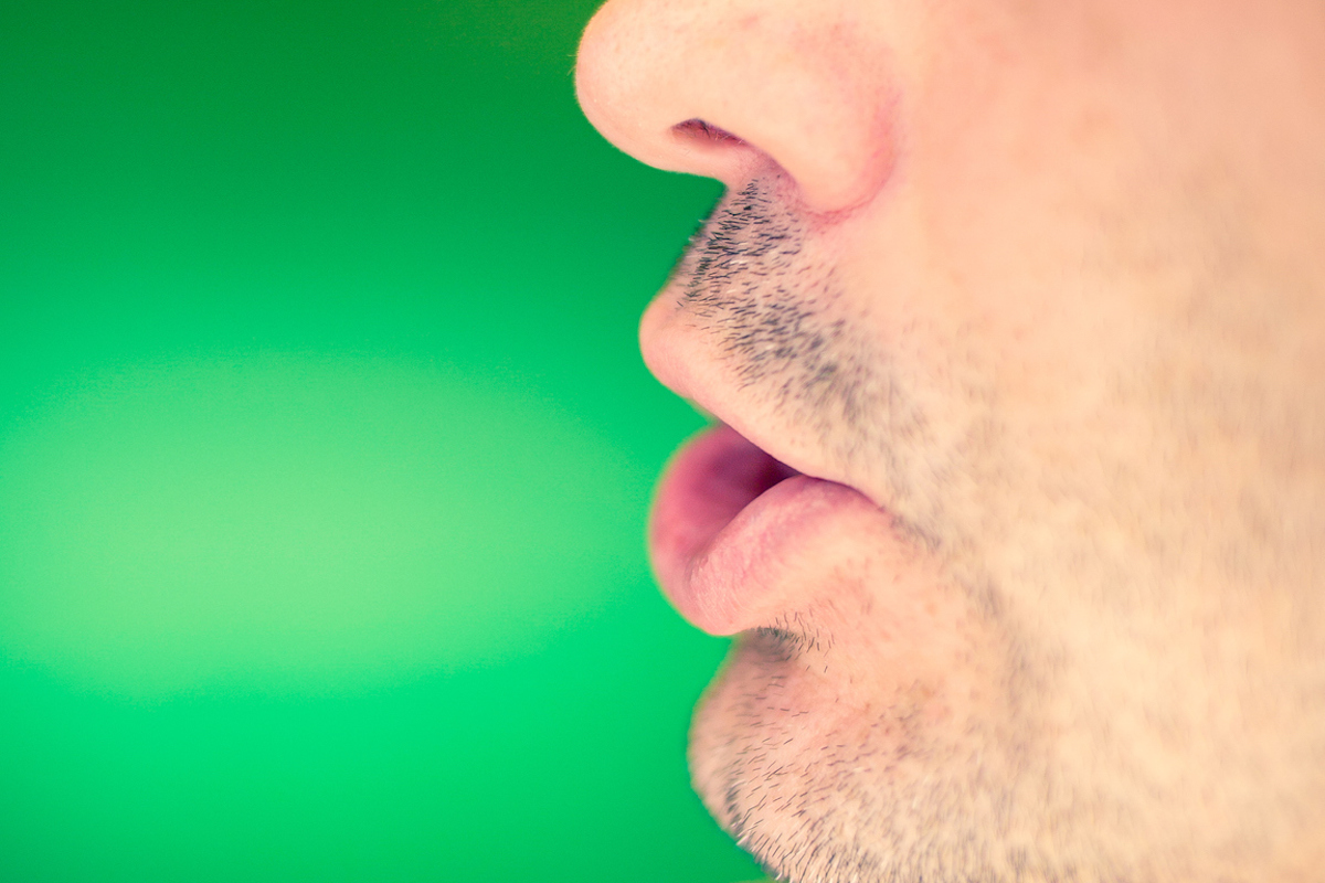 Man's lower part of face mid-word on green background
