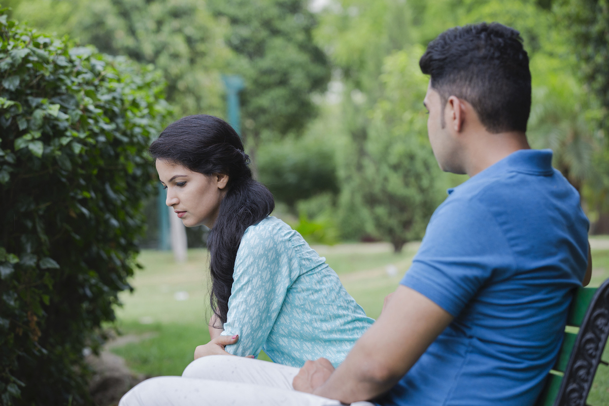 man and woman argue on park bench