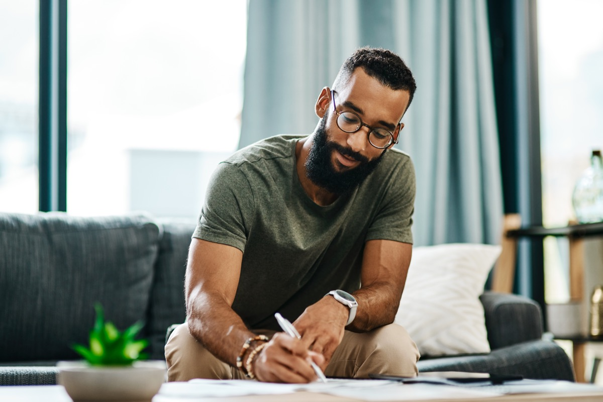 Man sitting on couch and writing
