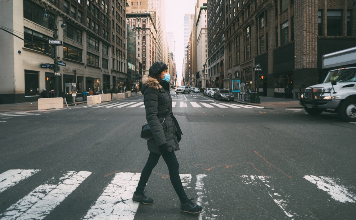 Woman wearing a mask crossing the street in NewYork City