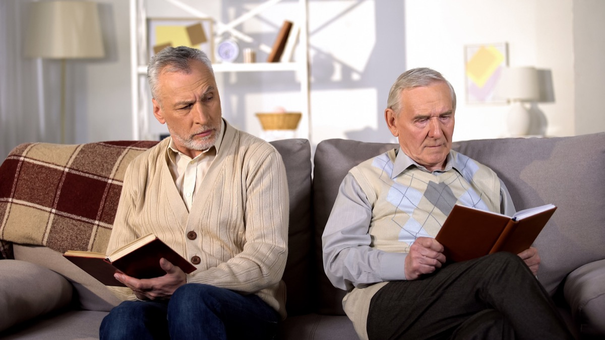 Two offended male friends reading books on sofa at home