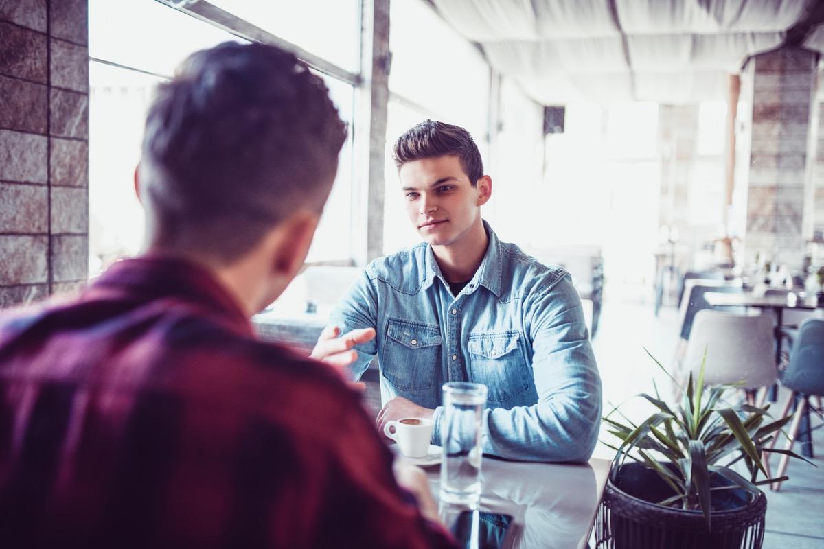 men Having tense conversation over coffee