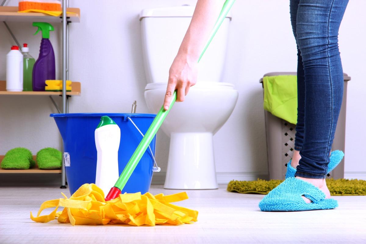 Mopping bathroom floor in slippers