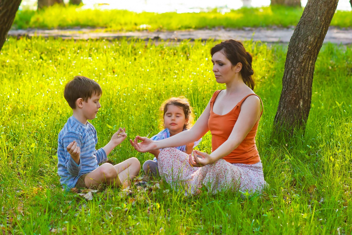 white mother and children meditating in grass