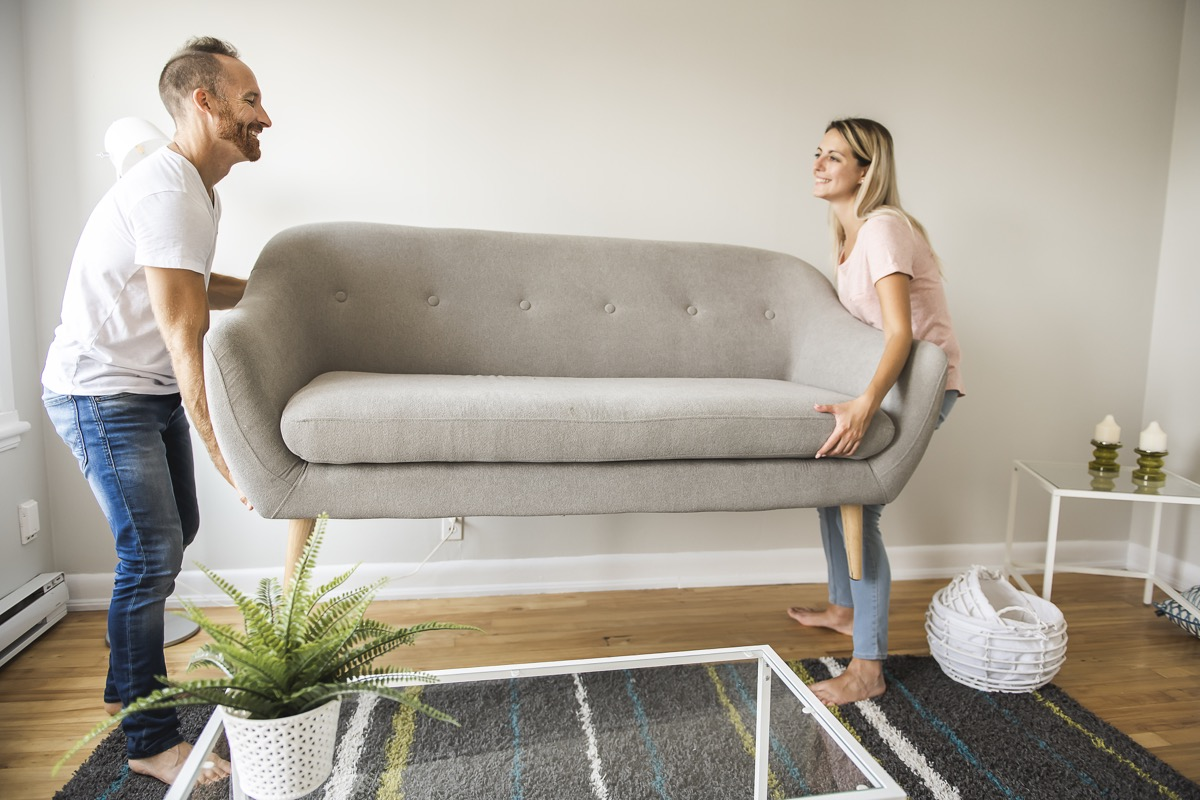 A Full length of happy couple placing sofa in living room of new home