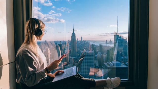 girl sits on windowsill overlooking nyc skyline