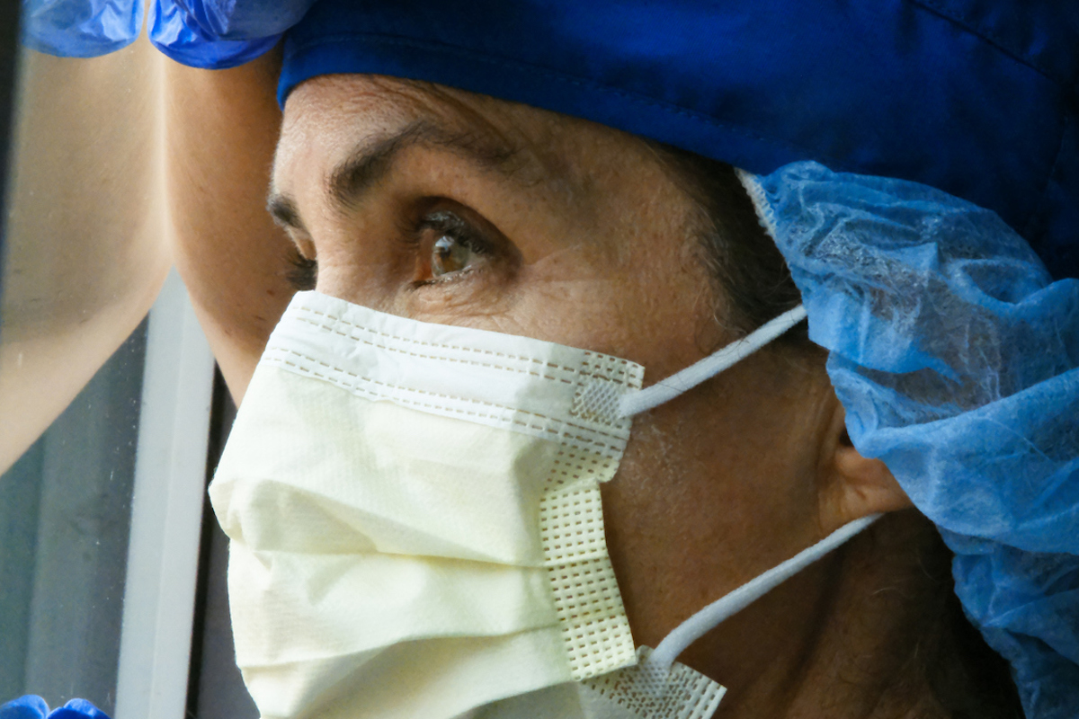 Overworked woman health care worker looking through a window while wearing a mask