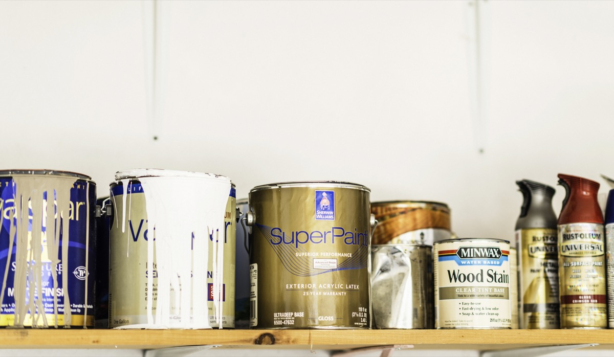 Suffolk, Virginia, USA - June 15, 2014: A horizontal shot of a collection of opened and unopened American brand cans of paint, wood stain and paint sprays organized neatly on a wooden shelf. The brands include cans of indoor house paint by Sherwin Williams and Valspar, spray paint by Rustoleum, and wood stain by Minwax.