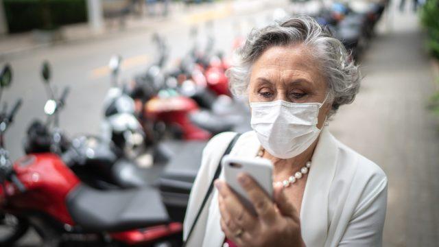 Senior woman with mask walking using phone on street