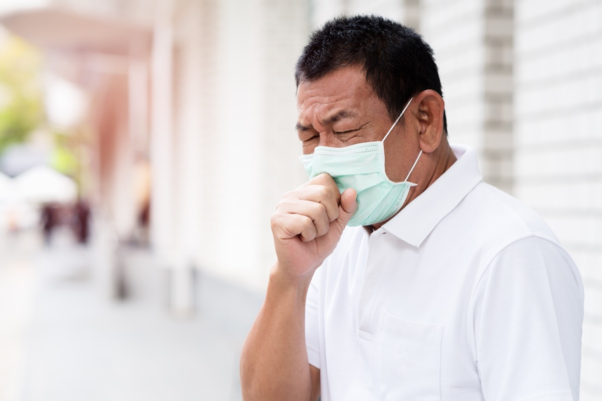 older asian man wearing face mask and coughing