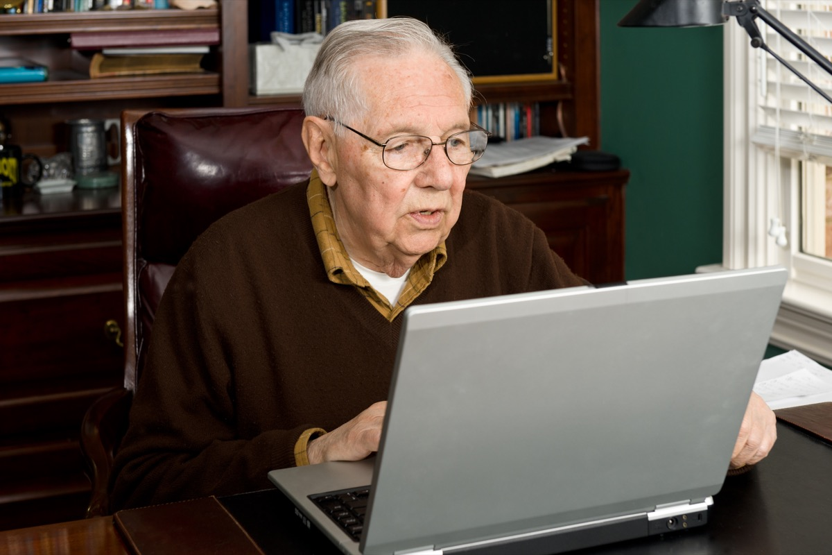 older man looking at laptop in home office