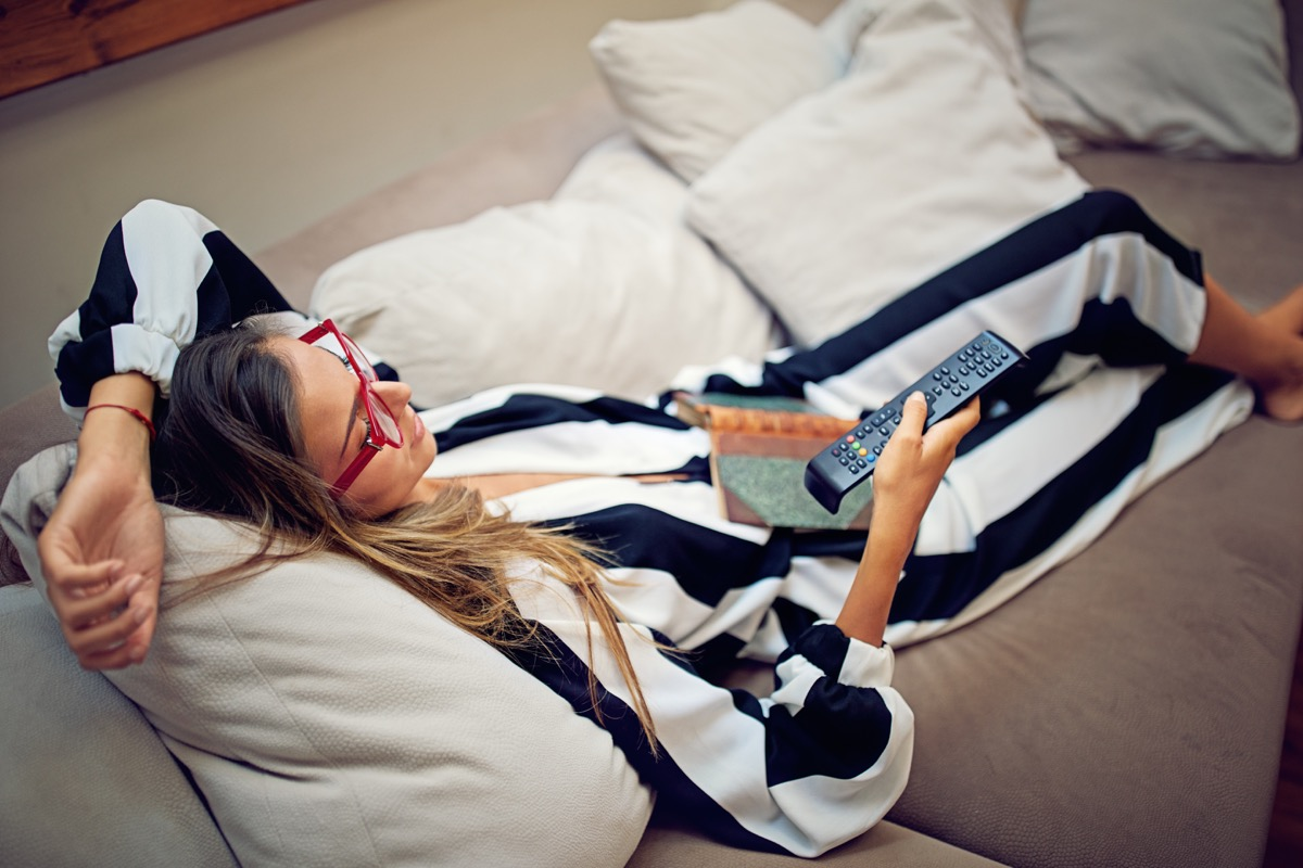 Young woman is lying on the sofa and watching TV