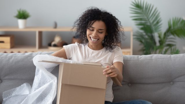 Woman opening box with a lot of bubble wrap on couch