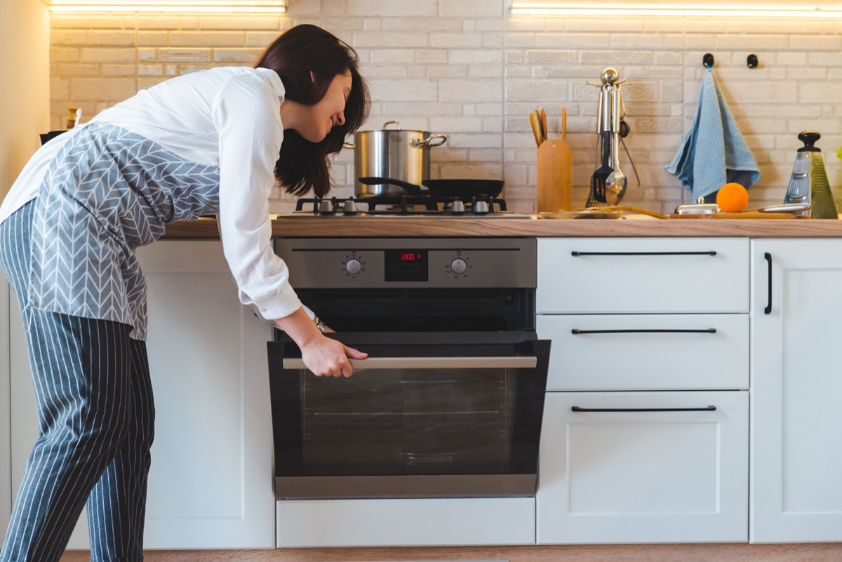 Woman using oven to cook