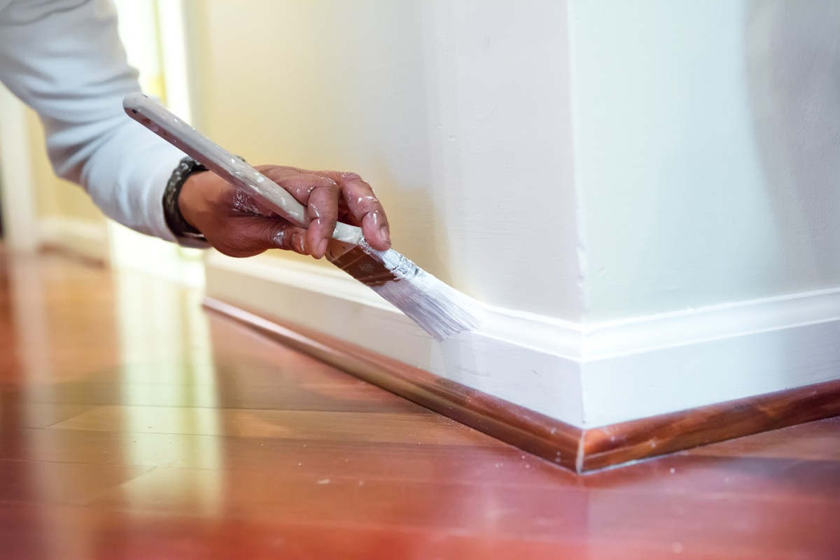 Painter is using a paint brush to paint baseboard in a home. RM
