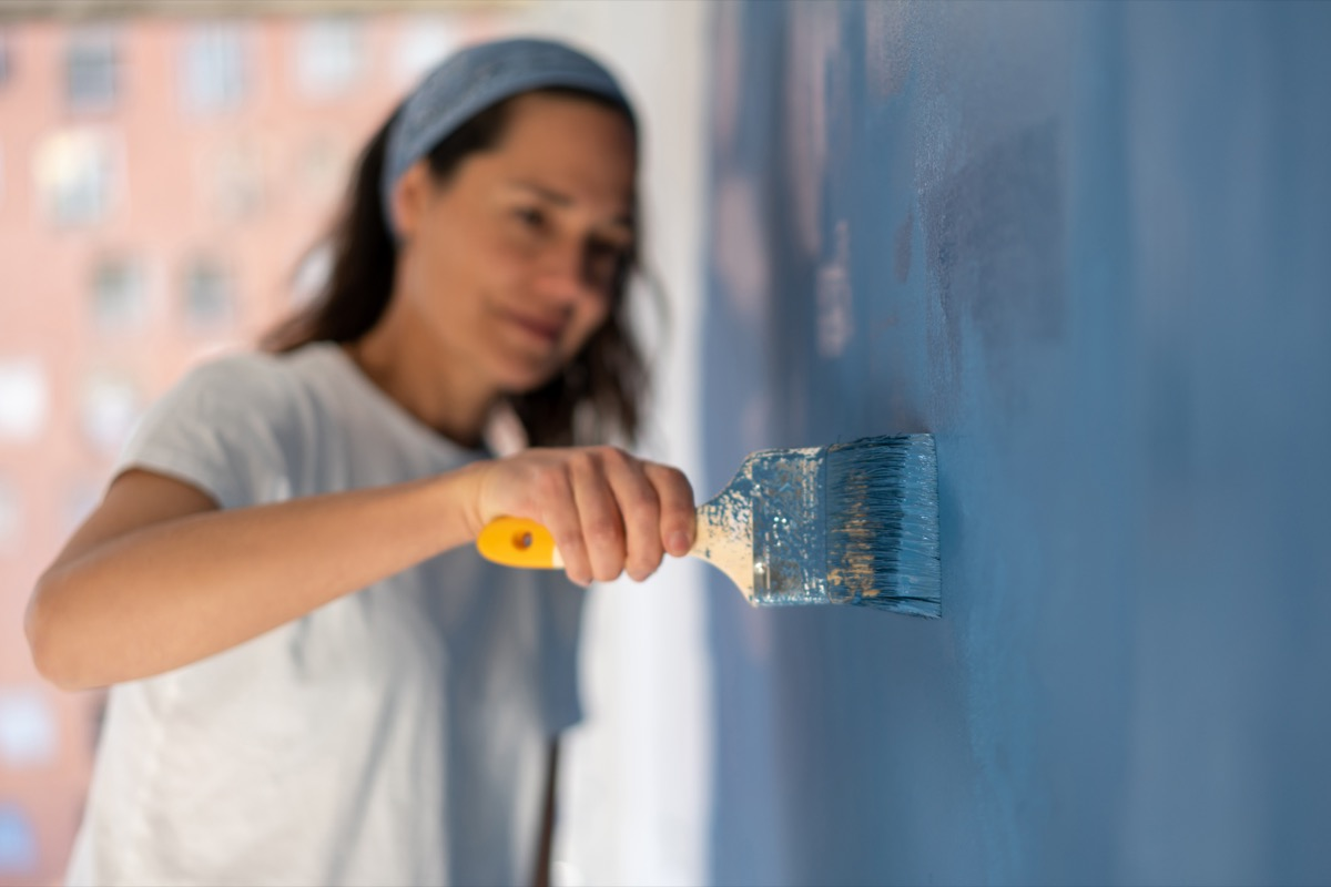 Close-up on a woman painting her house with focus on the brush – home improvement concepts