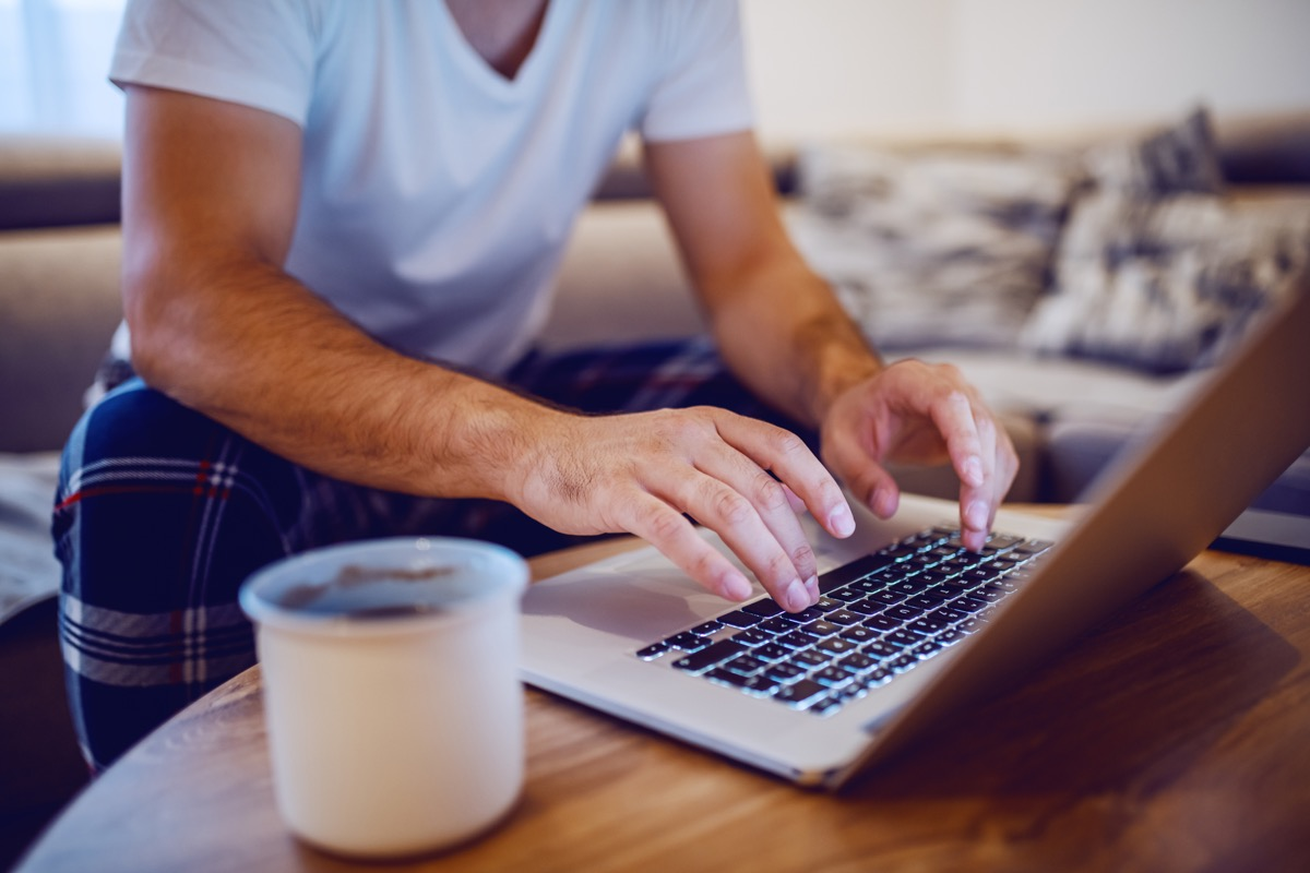 Cropped photo of man in pajamas typing on laptop keyboard and surfing the internet while sitting on sofa in living room in morning. Selective focus on hands.