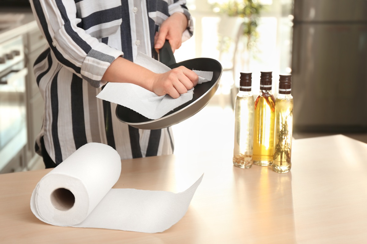 Woman using paper towel to dry frying pan
