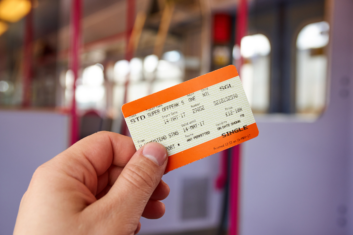 closeup of hand holding paper train ticket