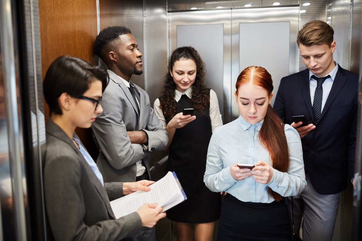 Young men and women using smartphones while standing in elevator of office