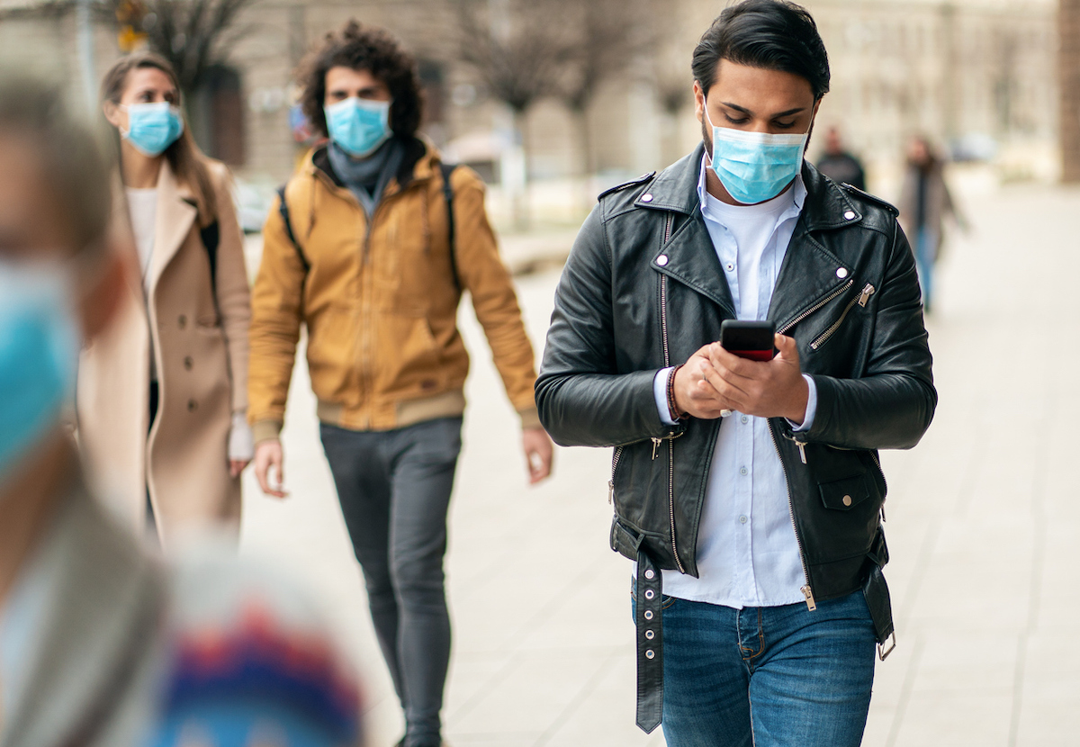 Portrait of young man on the street wearing face protective mask to prevent Coronavirus using smartphone