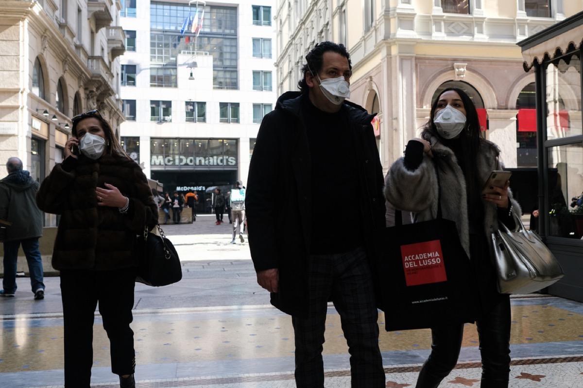 people walking on street in italy wearing masks to prevent coronavirus