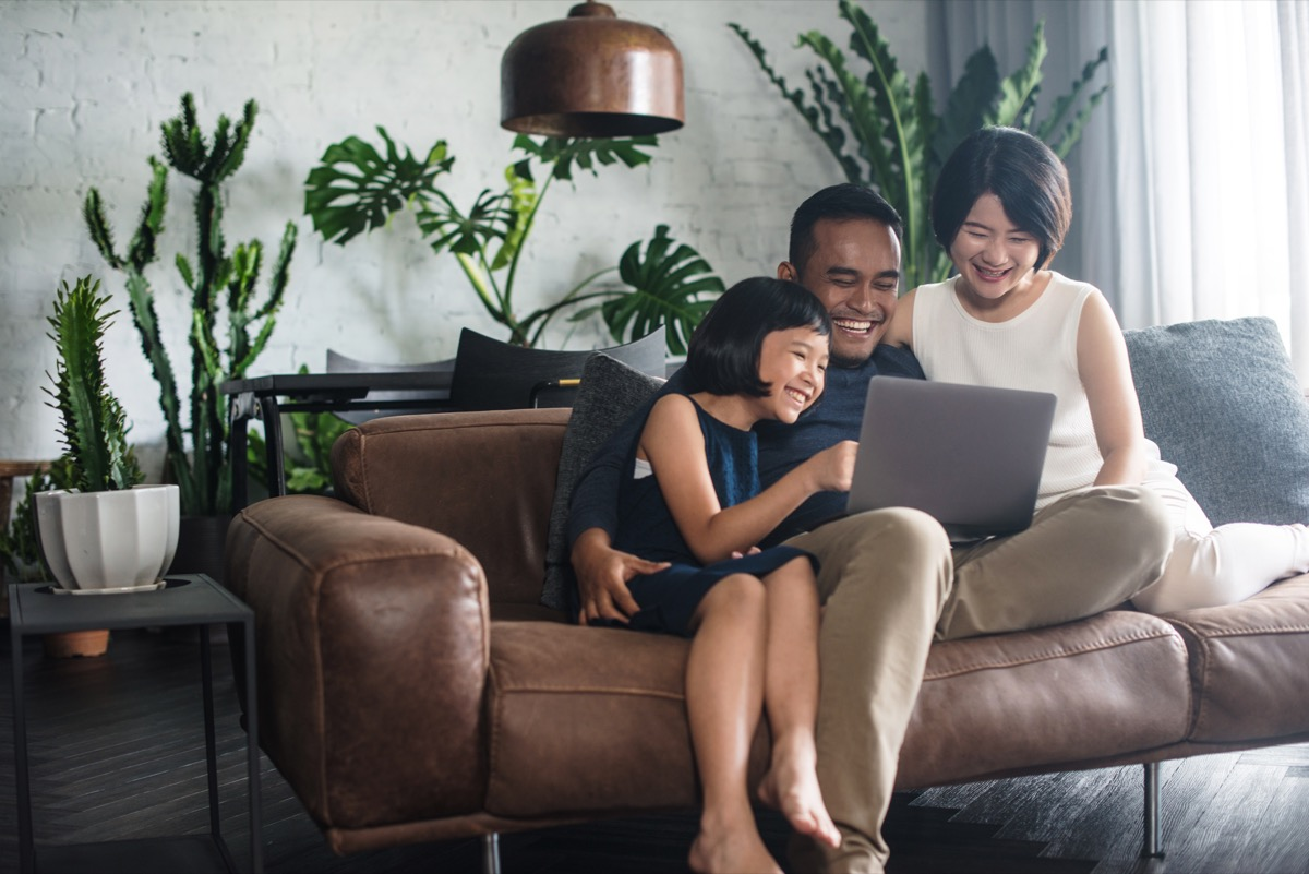 Family looking at laptop on couch together
