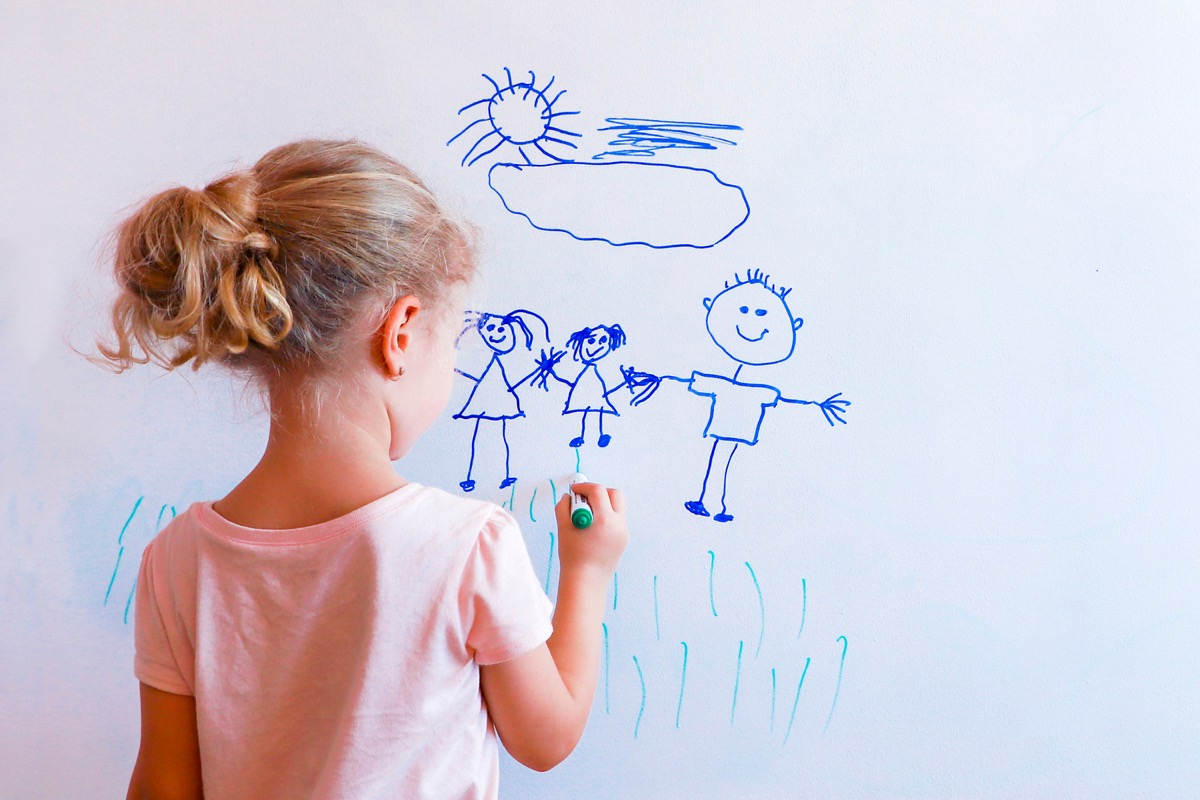 Young girl drawing picture on white board