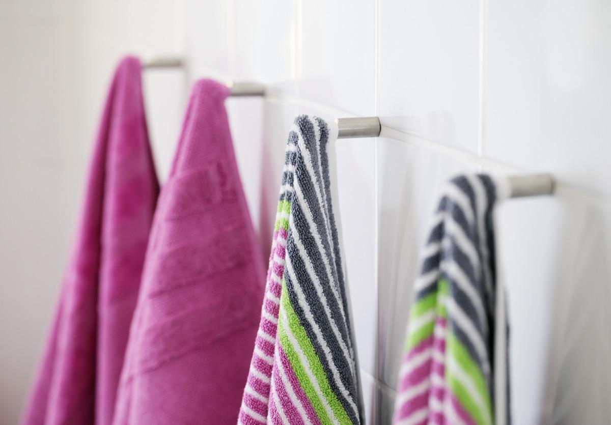 pink bath towels and striped bath towels on hooks