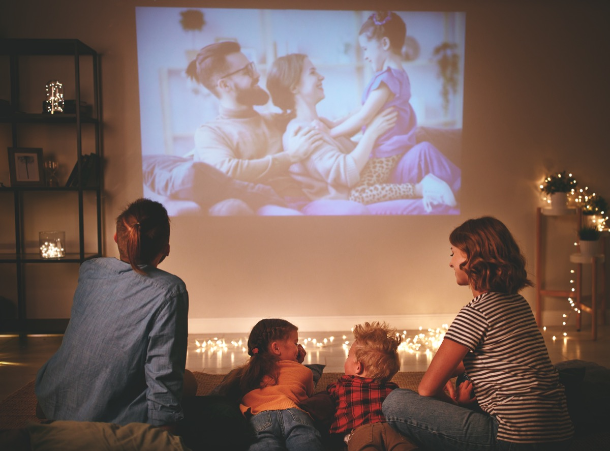 Family watching projector at home