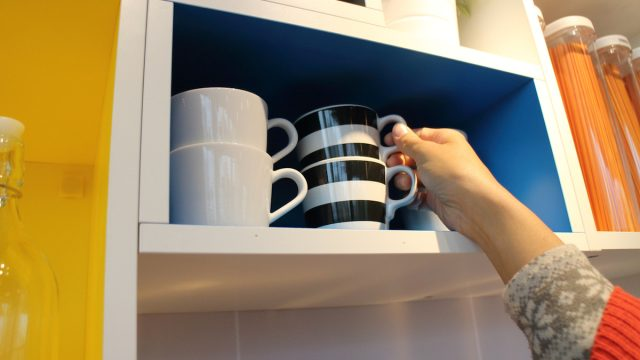 Woman's hand reaches for mug in kitchen cabinet