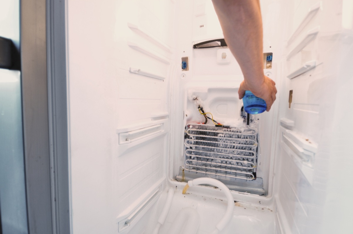 """""""Man's hand repairing fridge, pouring hot water over completely iced up element to thaw it quicklymore fridge repair shots"""""""