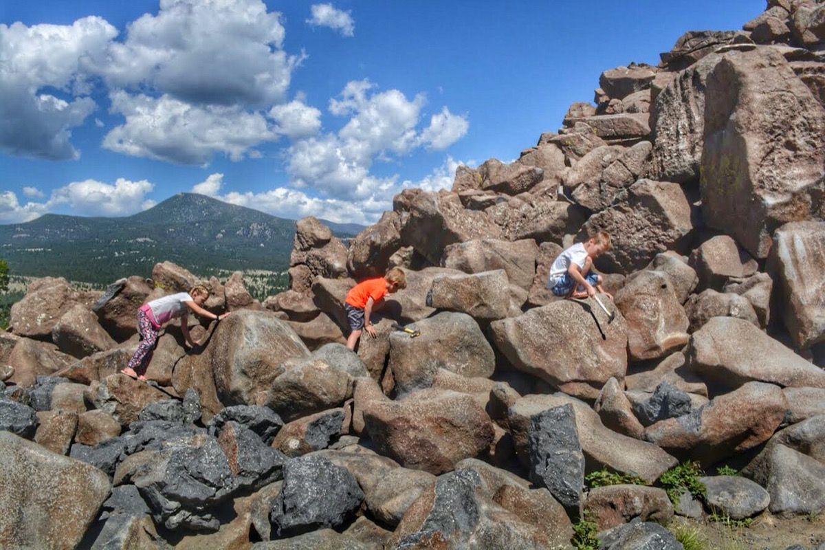 three children climb rocks and hit them with hammers
