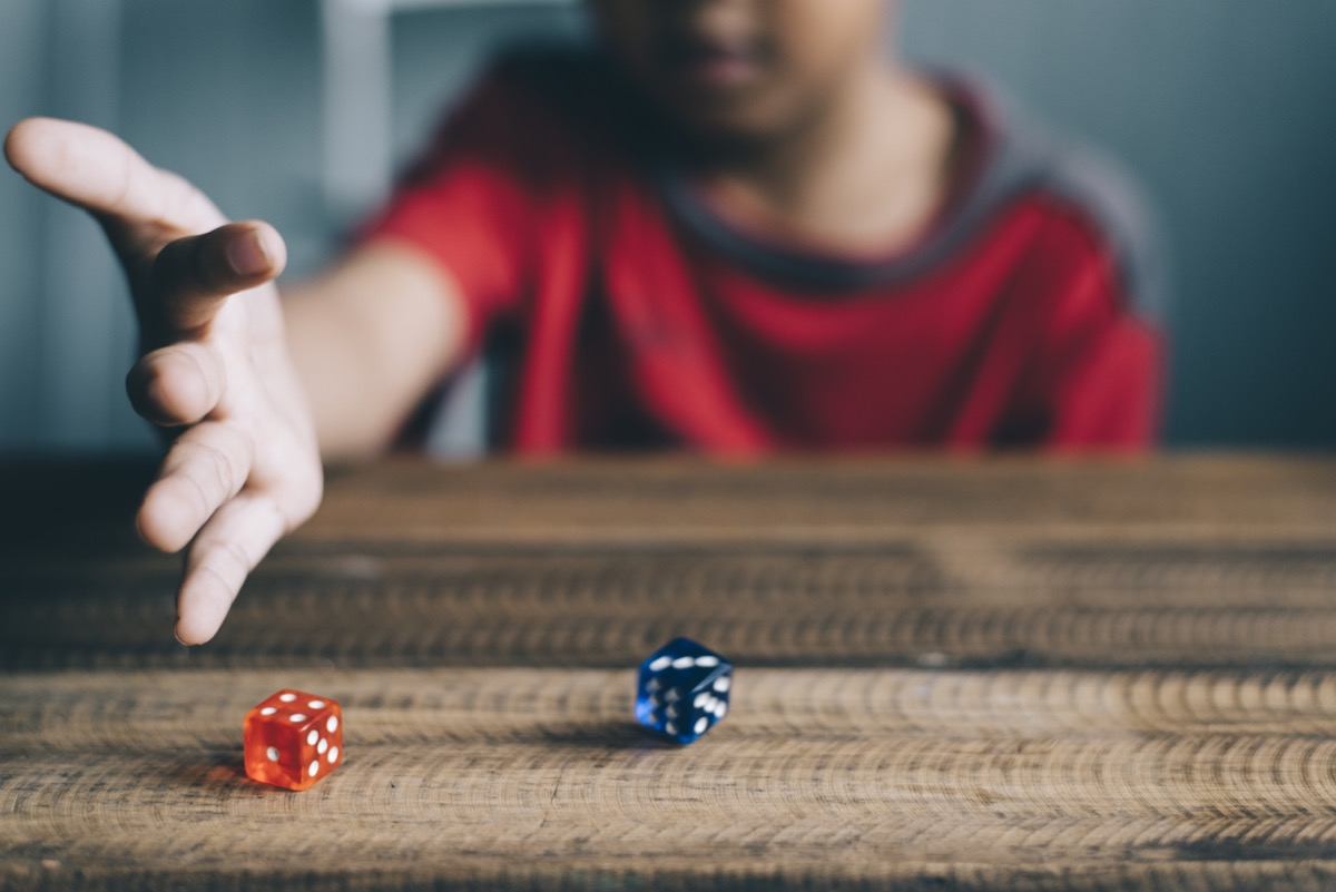 Kid rolling dice on table
